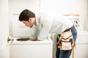 Profile view of a male technician inspecting and fixing a washer and dryer repair in a laundry room